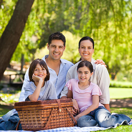 A family of four people sitting outside at a picnic in the woods