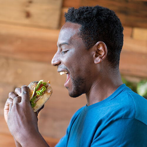 A profile of a man about to bite a delicious sandwich
