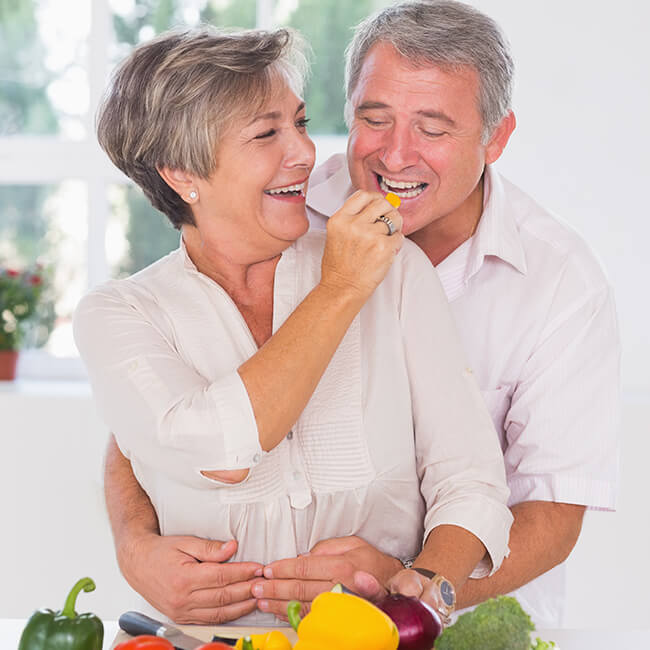 A happy elderly couple in the kitchen trying some food