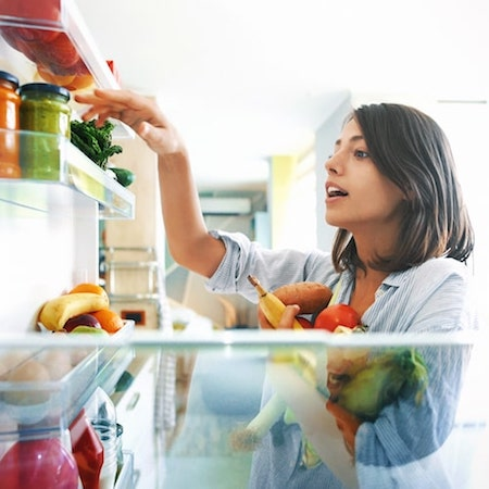A young women cleaning out her fridge with fruit and vegetables in her hand