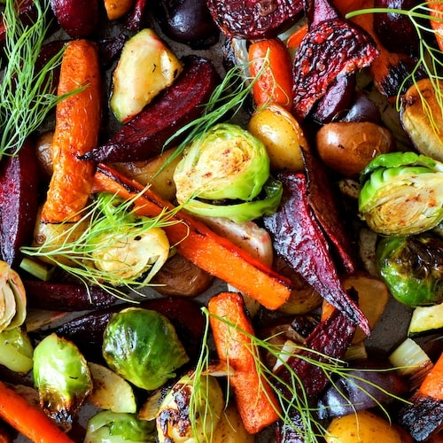 A close up picture of roasted carrots, beetrootm and brussel sprouts