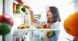 Woman choosing vegetables and ingredients from an open fridge