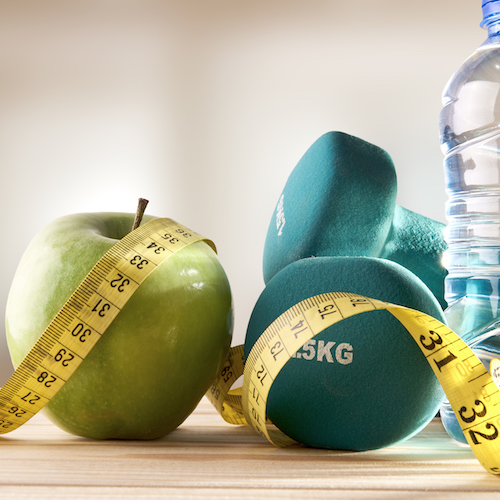 An apple, two weights, a bottle of water, and a measuring tape