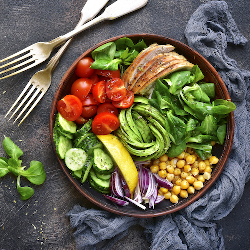 A bowl of salad, next to a knife and fork on a grey surface